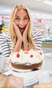 Szczęśliwa kobieta z usta otwartym przed tortem
