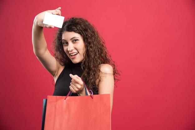 Szczęśliwa kobieta z wieloma torbami i kartą bankową na czerwono