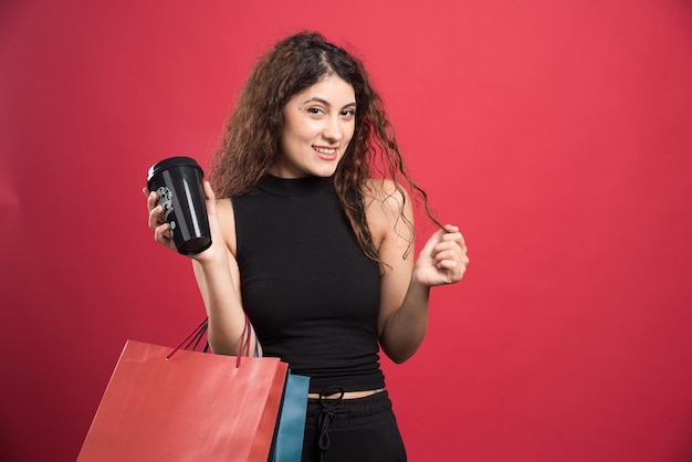 Szczęśliwa kobieta z wieloma torebkami i filiżanką na czerwono