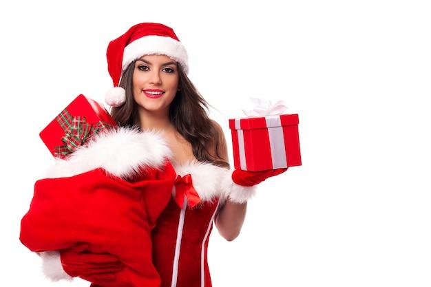 Szczęśliwa kobieta z worek świętego mikołaja pełen świątecznych prezentów