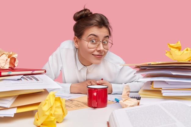 Szczęśliwa kobieta z zadowolonym wyrazem twarzy, ma zawiązane włosy, patrzy z zaciekawieniem, próbuje coś usłyszeć, nosi okulary i białą koszulę