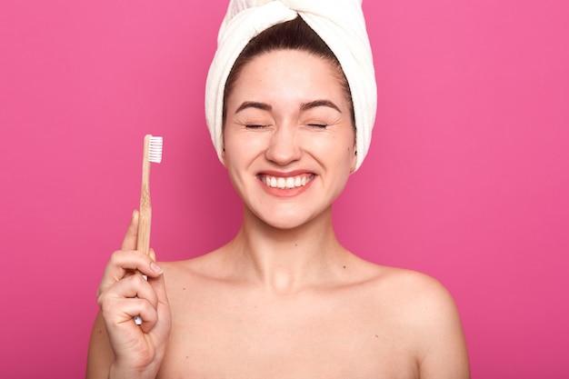 Szczęśliwa kobieta z zamkniętymi oczami, pokazuje białe zęby, pozuje nagimi ramionami, ma biały ręcznik na głowie