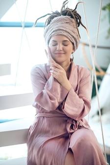 Szczęśliwa kobieta z zamkniętymi oczami siedząca w pobliżu okna