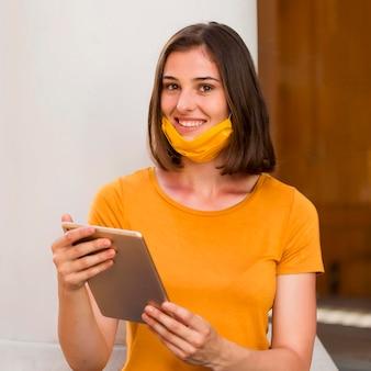 Szczęśliwa kobieta z żółtą maską medyczną