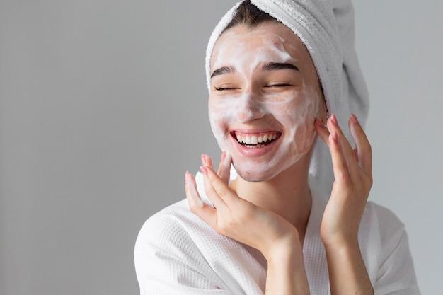 Szczęśliwa kobieta za pomocą produktu do twarzy
