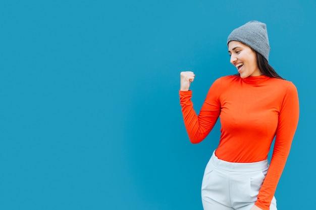 Szczęśliwa kobieta zaciska pięści jest ubranym dzianina kapelusz z kopii przestrzenią