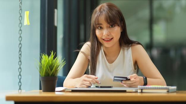 Szczęśliwa kobieta zainstalowała kartę kredytową, aby zapewnić koncepcję zakupów online w internecie