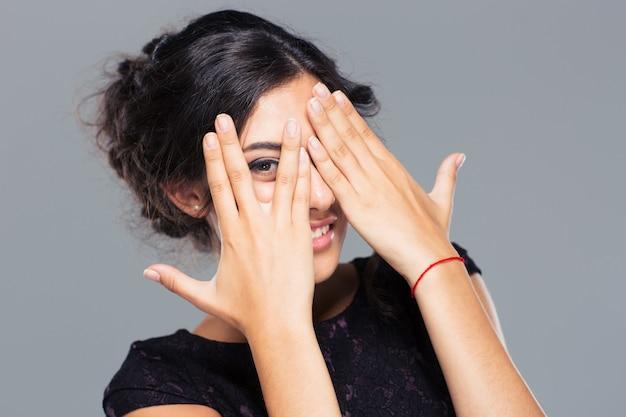 Szczęśliwa kobieta zakrywając jej oko palcem