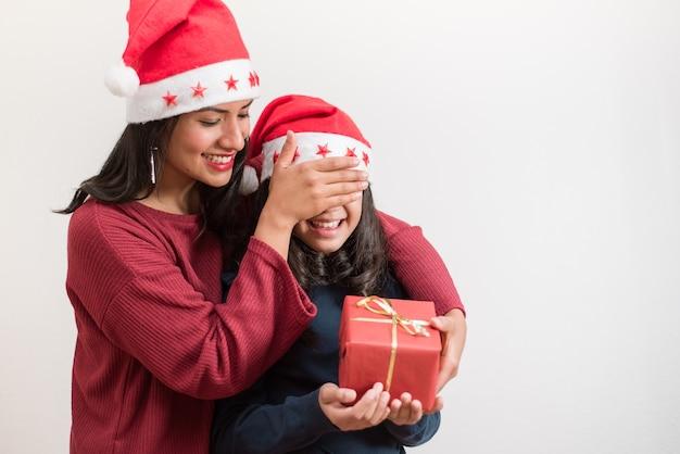 Szczęśliwa kobieta zakrywająca oczy i dając prezent jej małej dziewczynki.