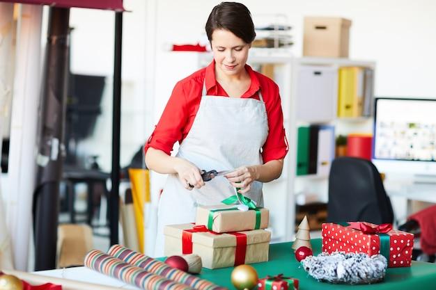 Szczęśliwa kobieta zawijająca prezenty świąteczne lub prezenty