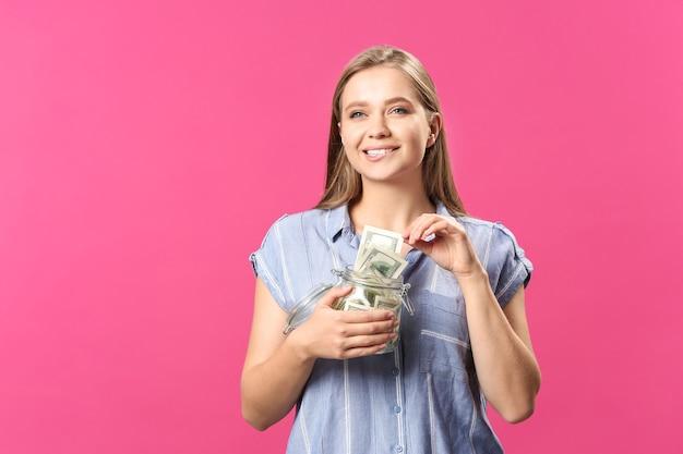 Szczęśliwa kobieta ze słoikiem pełnym banknotów dolarowych na różowo