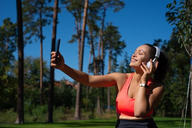 Szczęśliwa kobieta ze słuchawkami siedzi na sosnowym parku, słucha muzyki i robi selfie