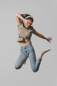 Szczęśliwa kobieta ze słuchawkami skoki w powietrzu