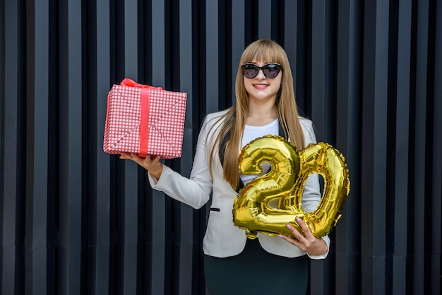 Szczęśliwa kobieta ze złotymi balonami i pudełkiem upominkowym pozuje na abstrakcyjnym ciemnym tle