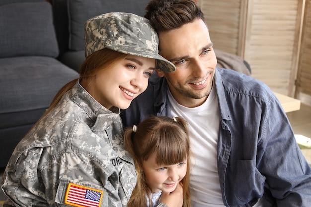Szczęśliwa kobieta żołnierz z rodziną w domu