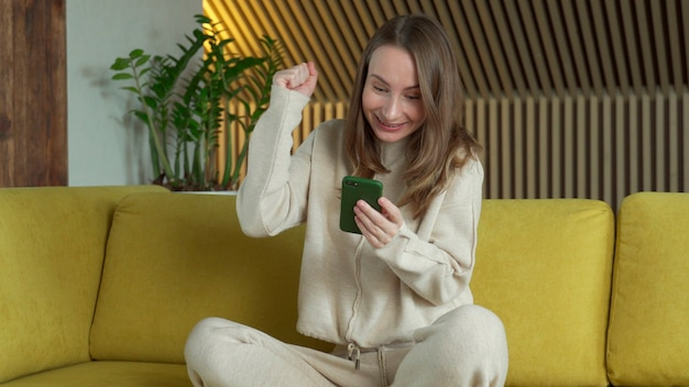 Szczęśliwa kobieta zwycięzca trzymając smartfon czytając wiadomość świętuje mobilne zwycięstwo, używając telefonu komórkowego siedzieć na kanapie w domu.
