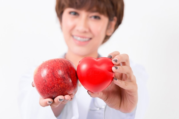 Szczęśliwa kobiety lekarka trzyma czerwonego jabłka i serce. koncepcja zdrowego i medycznego