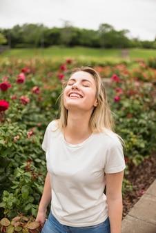 Szczęśliwa kobiety pozycja w kwiatu ogródzie