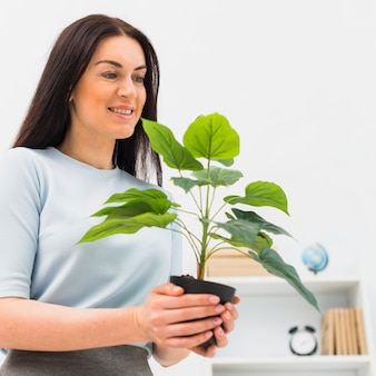 Szczęśliwa kobiety pozycja z zieloną rośliną w kwiatu garnku