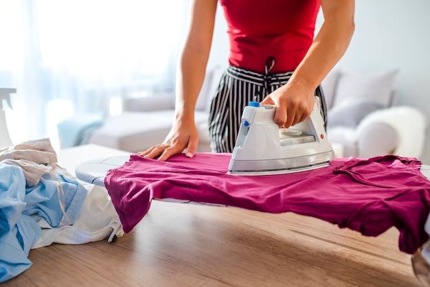 Szczęśliwa kobiety pozycja za deskową prasowanie odzieżą