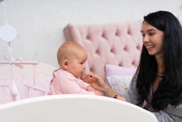 Szczęśliwa, kochająca mama bawiąca się z dzieckiem w różowym łóżeczku z wiszącą karuzelą.