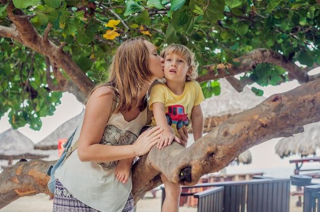 Szczęśliwa kochająca młoda matka całuje jej berbecia syna na spacerze