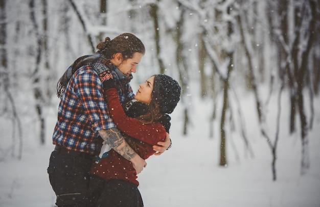 Szczęśliwa kochająca para chodzi w śnieżnym lesie