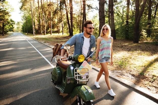 Szczęśliwa kochająca para chodzi z hulajnoga outdoors