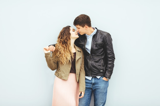 Szczęśliwa kochająca para odizolowywająca na szarym tle. stylowy wizerunek, dobry nastrój, zakochany pocałunek.