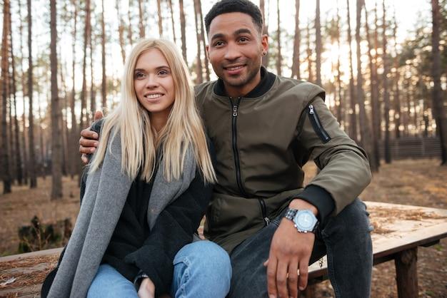 Szczęśliwa kochająca para siedzi outdoors w lesie