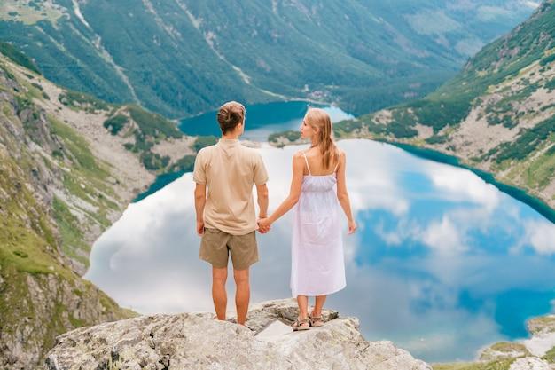 Szczęśliwa kochająca para stoi wpólnie przy kamieniem w wysokim tatrzańskim parku narodowym w polska z malowniczym krajobrazem na tle.