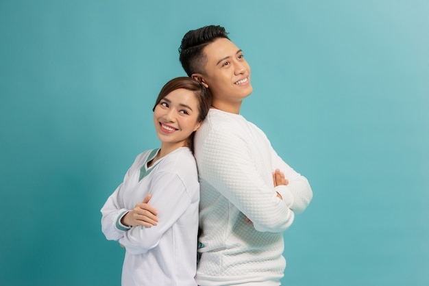 Szczęśliwa kochająca para. studio strzałów pięknej młodej pary stojąc tyłem do siebie i uśmiechając się
