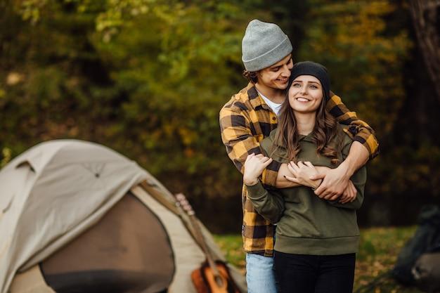 Szczęśliwa kochająca para turystów w lesie w pobliżu namiotu
