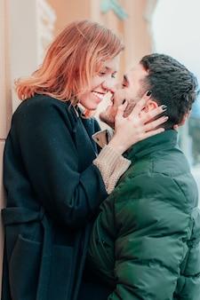 Szczęśliwa kochająca para, uśmiechając się i przytulając na ulicy. historia miłosna dwojga szczęśliwych ludzi - średni portret z bliska