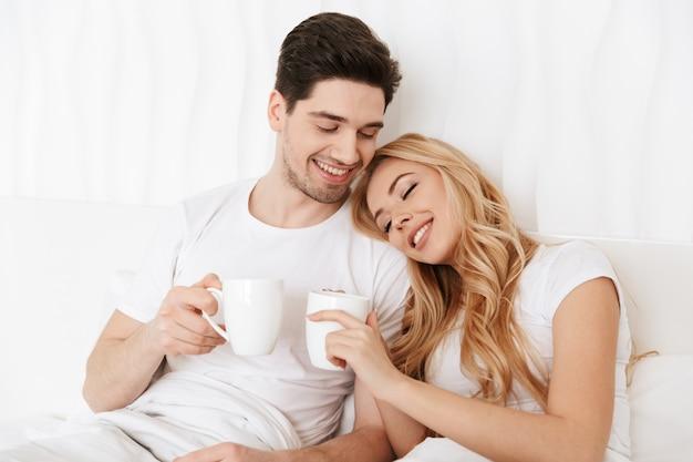 Szczęśliwa kochająca para w łóżku indoors w domu