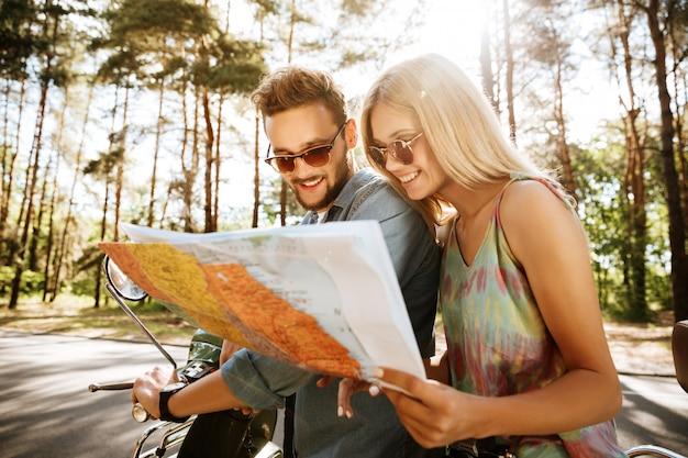 Szczęśliwa kochająca pary mienia mapa outdoors blisko hulajnoga