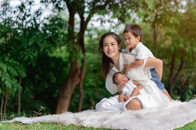 Szczęśliwa kochająca rodzina. azjatycka piękna matka i jej dzieci, nowonarodzona dziewczynka i chłopiec siedzi na trawniku, bawiąc się i przytulając w parku