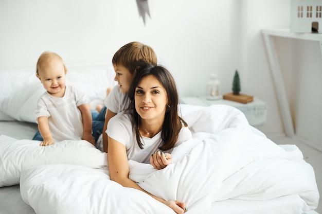 Szczęśliwa kochająca rodzina. matka bawi się z dziećmi w sypialni