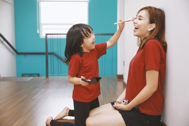 Szczęśliwa kochająca rodzina matka i córka bawią się, córka robi makijaż na matce, siedzą na drewnianej podłodze