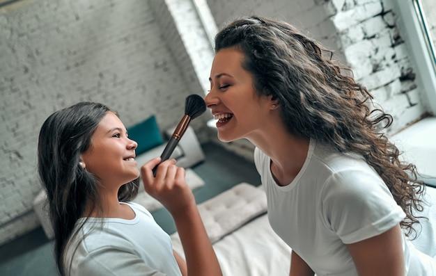 Szczęśliwa kochająca rodzina. matka i córka robi makijaż, siedząc na łóżku w sypialni.