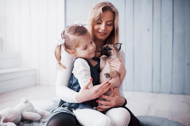 Szczęśliwa kochająca rodzina. matka i jej córka dziecko dziewczynka gra i tulenie uroczego mopsa
