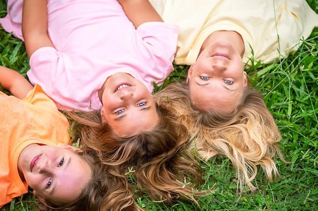 Szczęśliwa kochająca rodzina odpoczywa w parku. kobieta i dzieci dziewczynki leżą na plecach na trawie