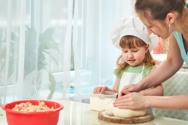 Szczęśliwa kochająca rodzinna narządzanie piekarnia wpólnie. mama uczy dziecko, jak gotować