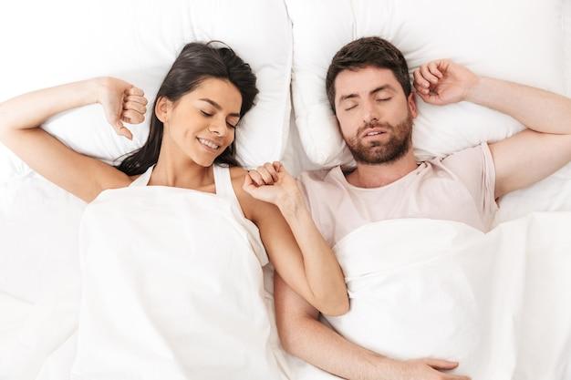 Szczęśliwa kochająca się para śpi w łóżku pod kocem