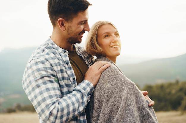 Szczęśliwa kochająca się para wędrująca i przytulająca się w górach