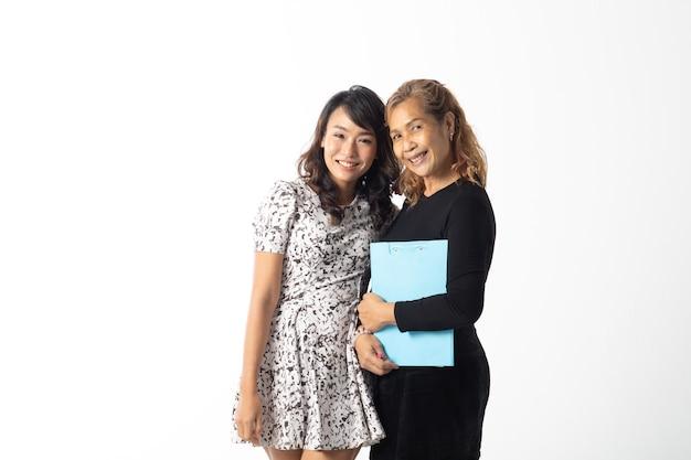 Szczęśliwa kochająca starsza matka i młoda córka śmieją się razem na białym tle