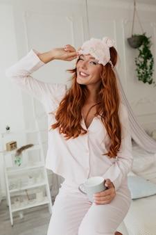 Szczęśliwa kochana kobieta z długimi falującymi włosami z maską do spania ubrana w piżamę z kawą rano w domu