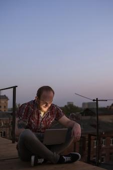 Szczęśliwa komunikacja w mediach społecznościowych na dachu. uśmiechnięty mężczyzna freelancer z laptopem na zewnątrz w centrum uwagi na pierwszym planie. tło miejskie z wolną przestrzenią, kreatywne samokształcenie