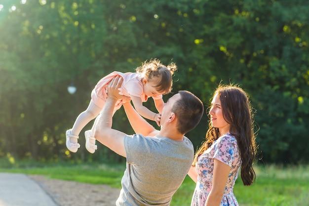 Szczęśliwa koncepcja rodziny - córka ojca, matki i dziecka, zabawy i gry w przyrodzie.