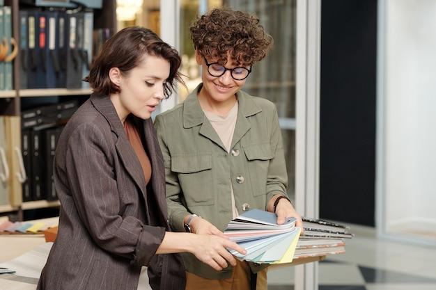 Szczęśliwa konsultantka studia wnętrzarskiego pokazująca konsumentom nowe próbki skór do mebli i doradzając, co kupić